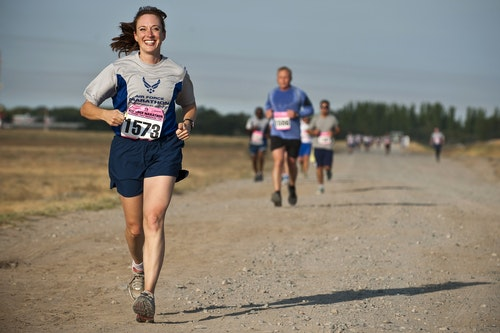 a woman looking very happy while running on a marathon